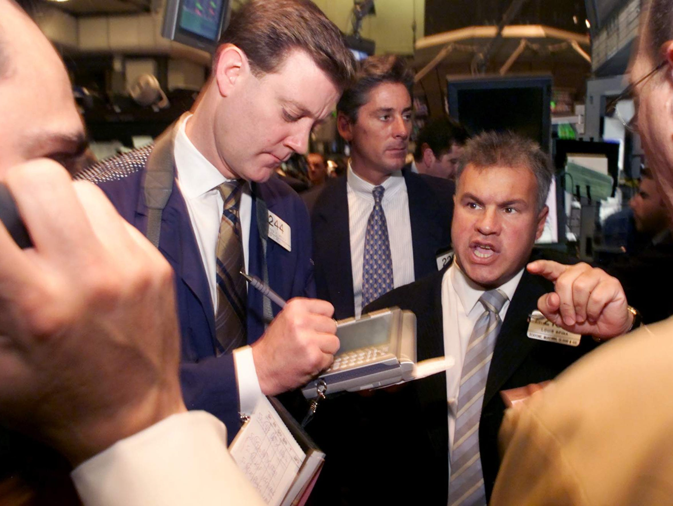 Louis Spina, second from right, conducts trading in