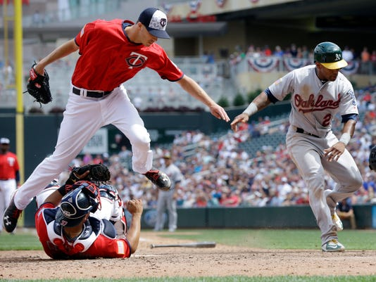 Minnesota Twins pitcher Tyler Rogers leaps over catcher Juan Centeno after Centeno tagged out Oakland Athletics' Khris Davis, right, at the plate on a fielder's choice in the seventh inning of a baseball game Monday, July 4, 2016, in Minneapolis. (AP Photo/Jim Mone)