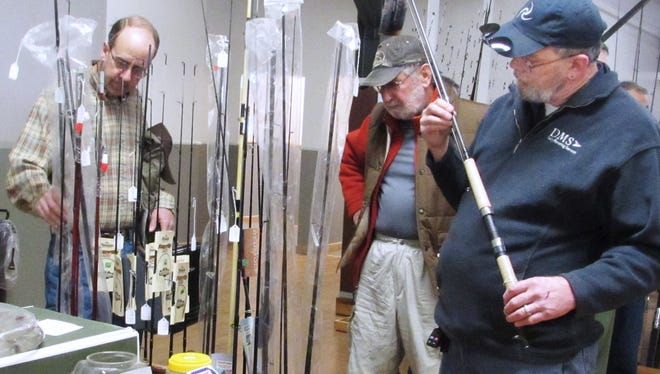 Kirt Howe, right, of Owego, and other visitors look over fishing rods during last year's annual fishing tackle flea market and outdoor show in Watkins Glen.