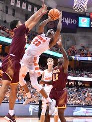 Syracuse guard Frank Howard (23) shoots around Iona