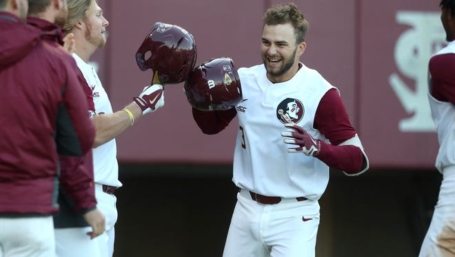 FSU's Nick Derr, center, is congratulated at home plate his teammates after hitting a 3-run home run against UCF at Dick Howser Stadium on Wednesday, March 21, 2018.