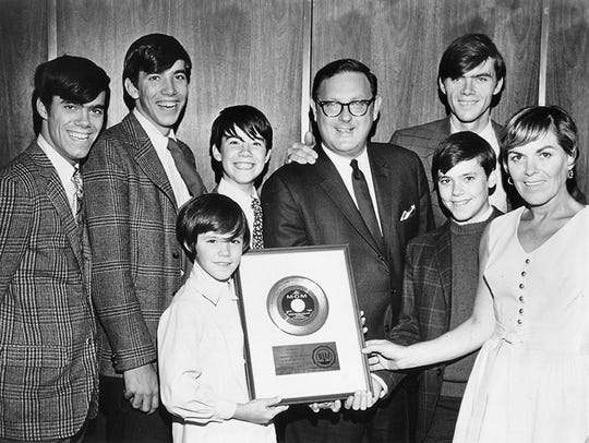 The Cowsills show off the gold record they received