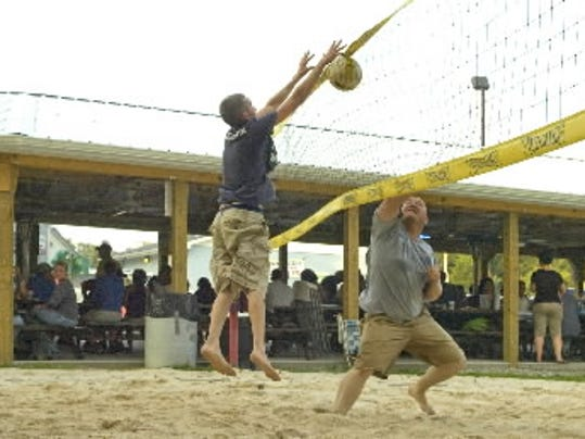 Brent Neal, right, and Noah Marcotte battle at the net during a game of two-on-two beach volleyball at Goofy s Eatery & Spirits in North Codorus Township. The restaurant also has horseshoe pits.