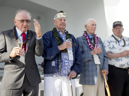 USS Arizona survivors, from left to right, Don Stratton, Lou Conter, John Anderson, and Lauren Bruner make a final toast during a ceremony on the USS Arizona Memorial at Pearl Harbor.