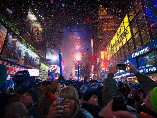 File: Revelers cheer under falling confetti at the stroke of midnight during the New Year's Eve celebrations in Times Square, Wednesday, Jan. 1, 2014, in New York.