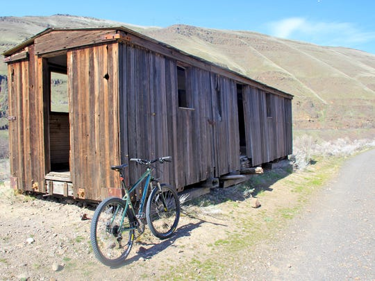 An old railroad car sits along the Lower Deschutes