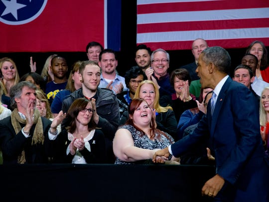 President Obama greets people on stage as he arrives