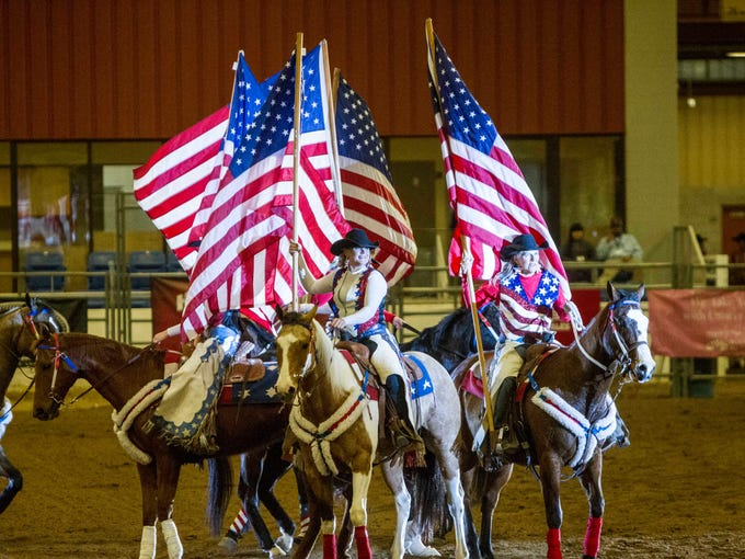 Cowgirls display the American flag before the start