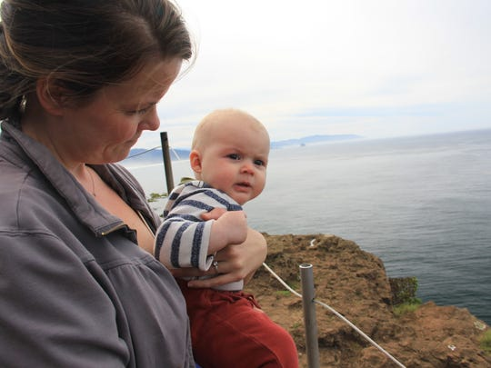 Five-month-old Lucy Urness and her mom Robyn Orr scan the horizon for signs of gray whales migrating past Cape Lookout on the Oregon Coast.