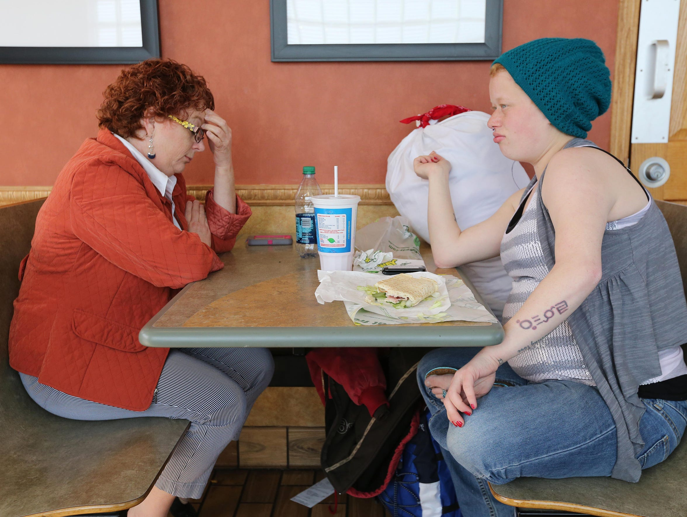 Lyzz Buford eats a sandwich at Subway with her mom,
