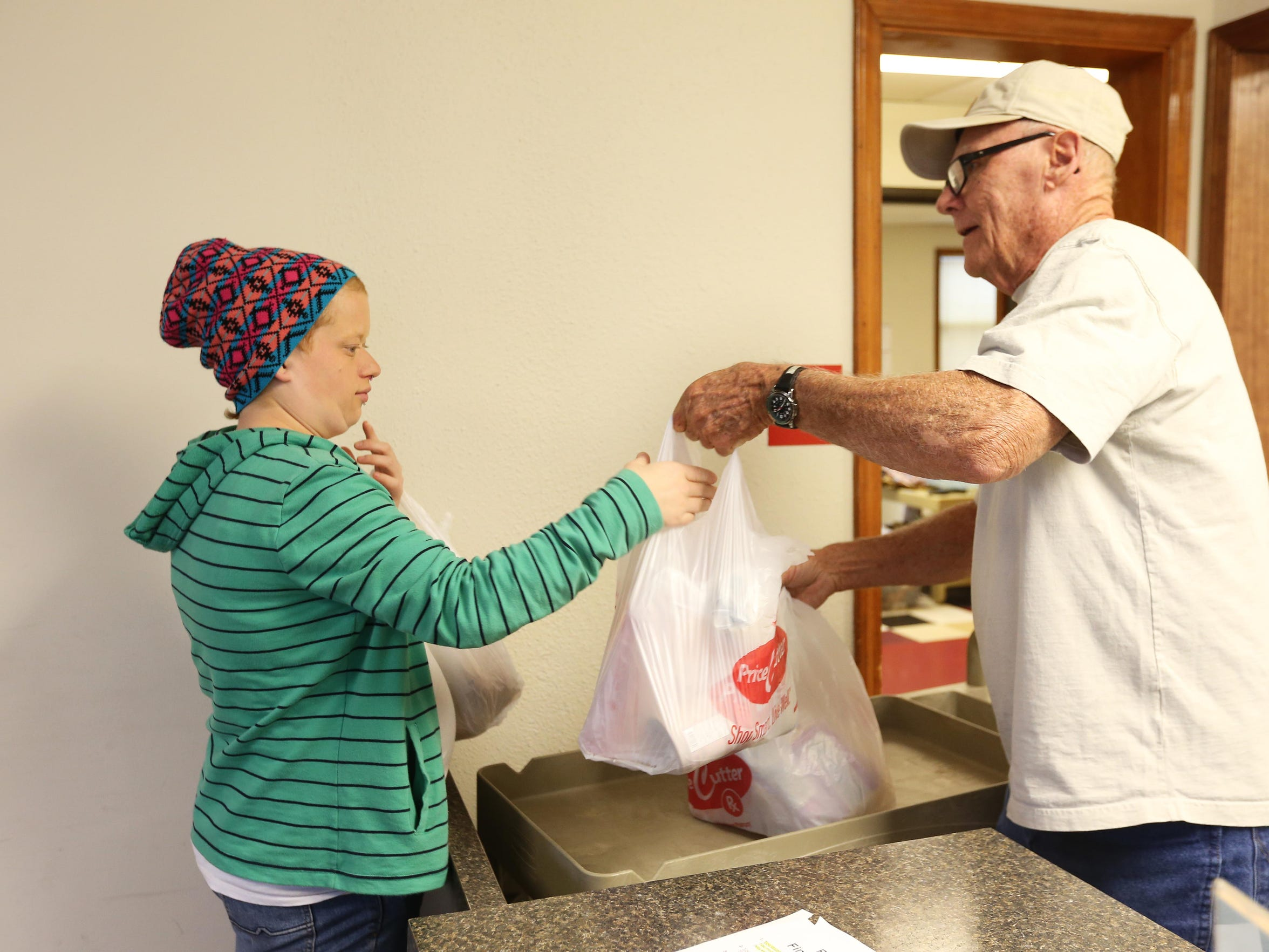 Lyzz Buford receives food from a volunteer at the Well