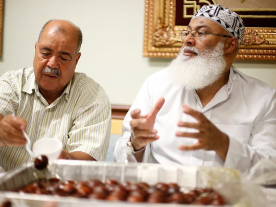 Imam Abdulla Amro, right, and Bashir Sheibani break their fast during a meal called Iftar, which literally translates to 'breakfast', at the Al-Furqan Mosque during Ramadan on Thursday, July 2, 2015.