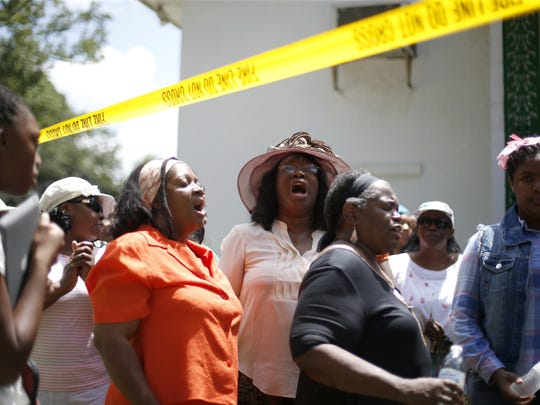 Greater Miracle Temple church members sing outside of the building on Saturday next to caution tape outlining the fire that destroyed the building late last month.
