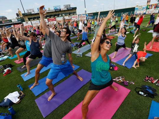 Julie Methlie of Urbandale (right) laughs as she and hundreds of yoga enthusiasts hold a pose Saturday, Aug. 8, 2015, during the Power Life Yoga at the Ballpark event in the outfield of Principal Park in Des Moines.