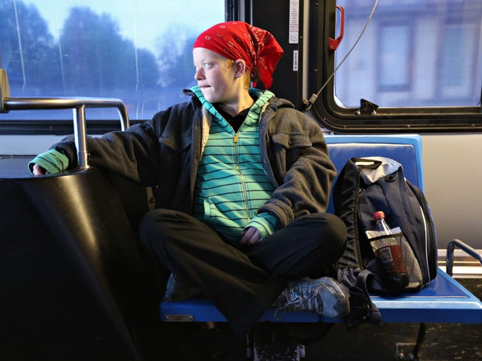 Lyzz Buford takes the 5:30 a.m. bus to work on April