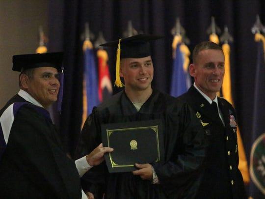 A graduate of Central Texas College is awarded his degree as Maj. Gen. Gary J. Volesky, right, observes Friday during the Graduation Celebration Ceremony at Fort Campbell.