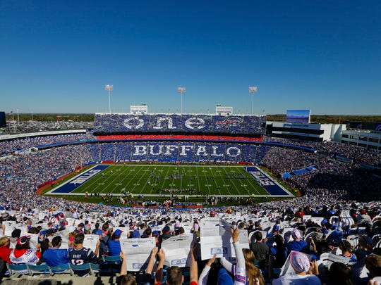Fans hold signs during a pre-game ceremony to announce new Buffalo Bills owners Terry and Kim Pegula, before an NFL game on Oct. 12, 2014.