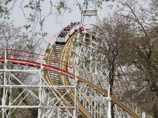 The Arnolds Park roller coaster cars descend the first hill in a photo from 2013.
