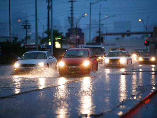 Cars drive through flood waters on Grand Ave in Phoenix,
