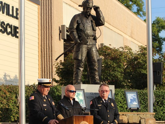 Clarksville Fire Chief Michael Roberts commends sculptor and firefighter, Scott Wise, center, and retired Capt. Danny Perry for their efforts after unveiling a new sculpture honoring fallen firefighters outside the main station.