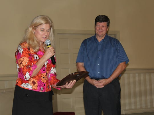 Lucy Hughes reads a plaque for presentation to Susannah Heschel at Saturday's program at River City Church. With her is her husband, Paul Hughes.