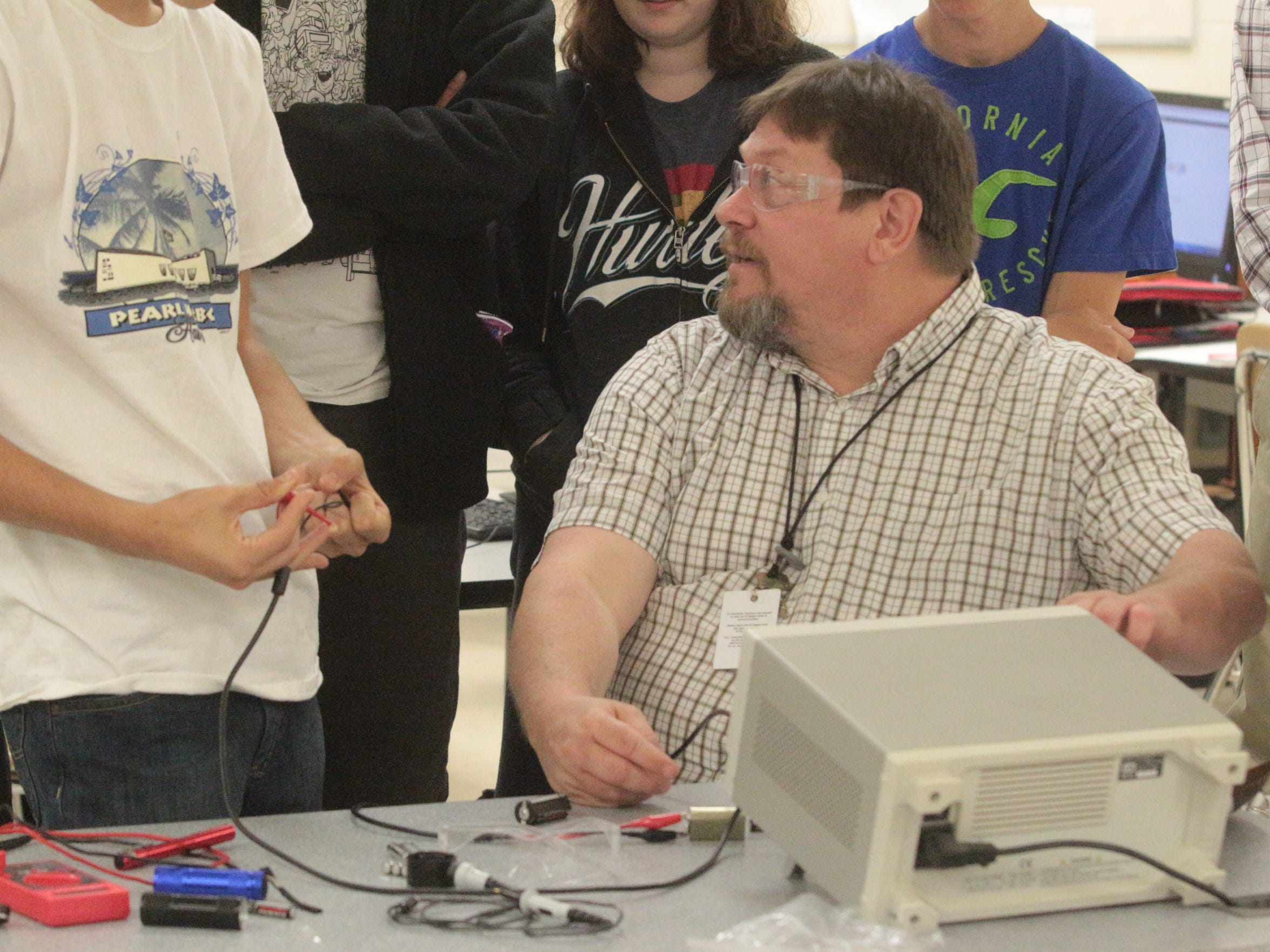 John Savage, mechatronics instructor with Nashville State Community College, teaches students Thursday at Kenwood High School about voltages using an oscilloscope.
