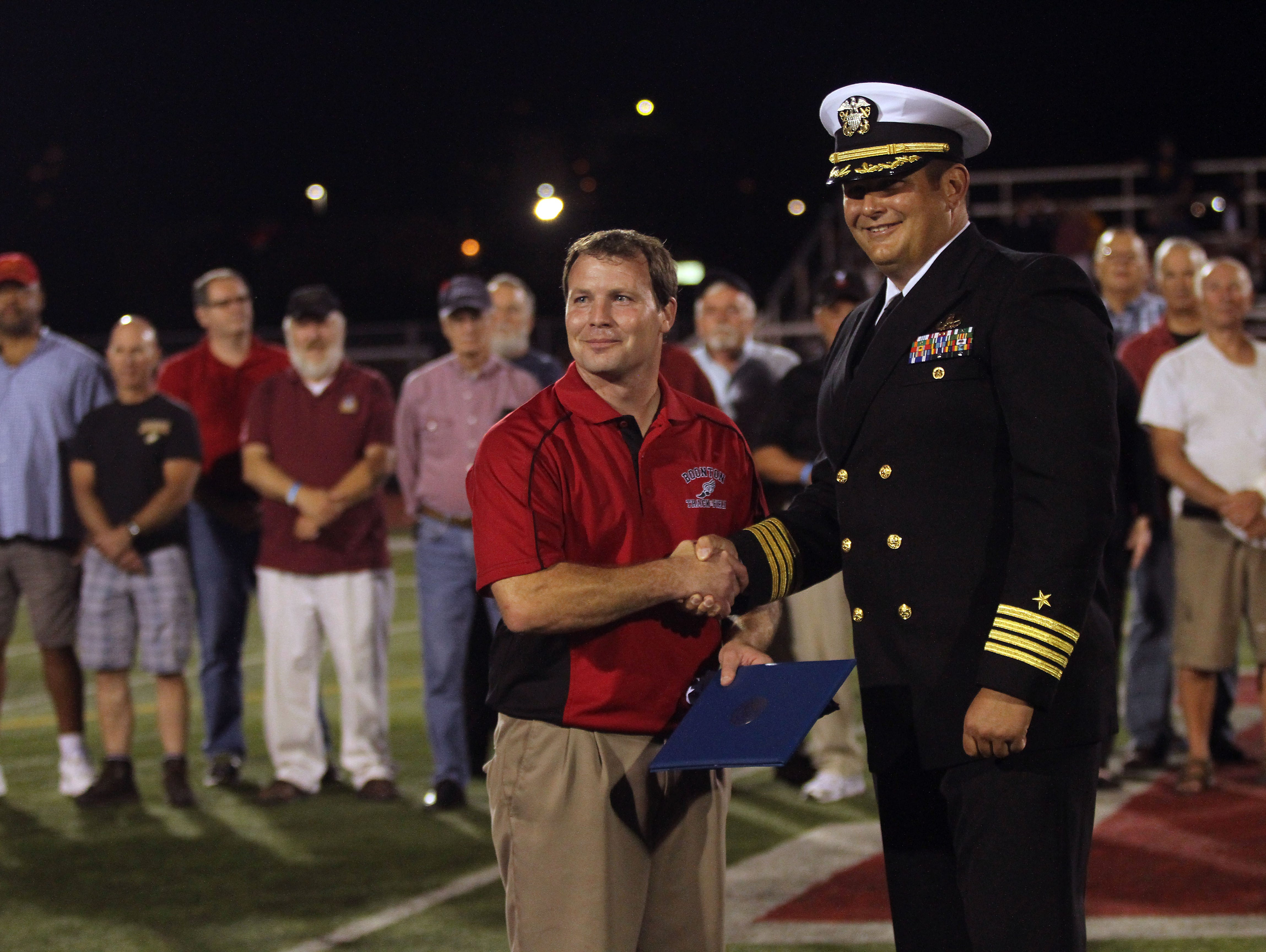 Boonton Athletic Director Dave Hughen, l, is presented an American flag flown over the Pentagon by Boonton grad, Navy Capt. Dean Muriano as Boonton High School honored its graduate military veterans during halftime of the Boonton High School football game Friday night. The vets, some of whom are still residents, others coming back from out of town, also enjoyed a tailgate party prior to the game and ceremony.