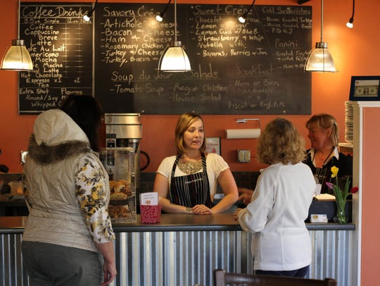 Danielle Baca, center, helps customers at Oregon Crepe