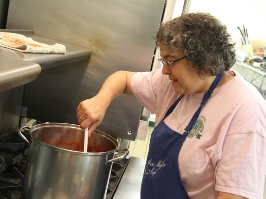 Beth Rankin makes pasta sauce in the commercial kitchen at McMinnville Cooperative Ministries.