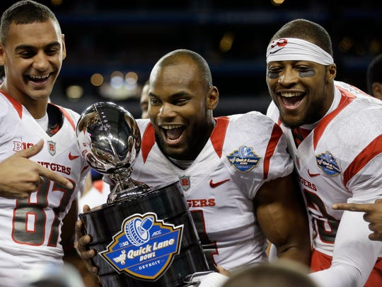 Rutgers wide receivers Vance Matthews (87), Leonte Carroo, center, and Carlton Agudosi flank the trophy after winning the 2014 Quick Lane Bowl.