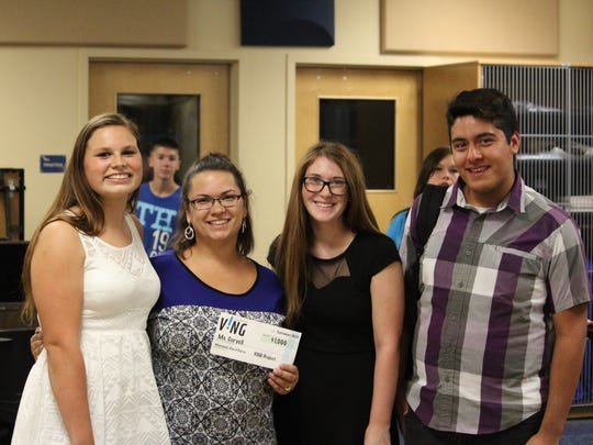 Kiarra Free, 16,  Makennah Eck, 16, and Elias Saldana, 17, honored their color guard instructor, Anne Coryell, with a $1,000 check on Thursday, Oct. 1, at Buckeye Union High School.