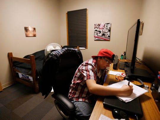 Mikey Fletcher of Omaha, Neb., finishes up homework