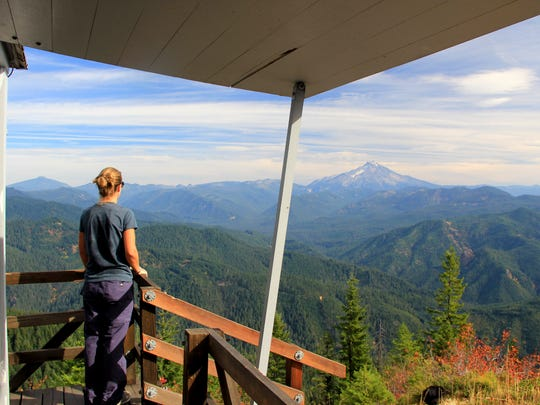 A hiker from Eugene looks out on Mount Jefferson from the deck of Gold Butte Lookout.
