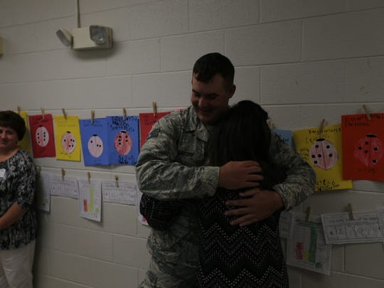 Staff Sgt. Douglas Carson II hugs his sister Amie Abel, right, after surprising her at David Youree Elementary School after returning home from his Air Force deployment. Their mother, Jewel Carson, left, looks on.