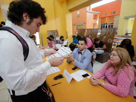In this Tuesday, Oct. 6, 2015, photo, Alexander Haupt, left, 21, of Miami, looks over his job application as he speaks with Brooks Brothers Factory Store assistant store manager Daniel Lago, center, and visual merchandiser Barbie Pacheco, right, during a job fair at Dolphin Mall in Miami. The U.S. Labor Department reports on the number of people who applied for unemployment benefits during the week ending Oct. 10 on Thursday, Oct. 15, 2015.