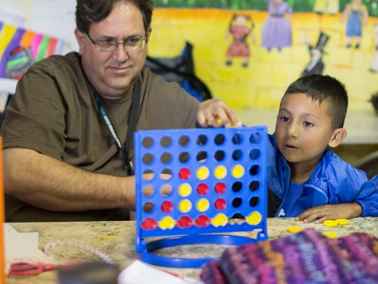 Ezequial Alvarado, 6, right, plays Connect Four with