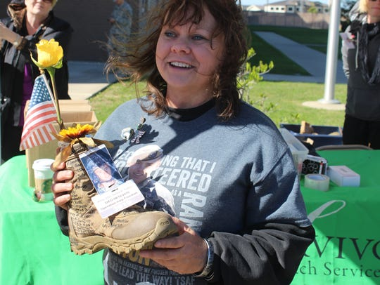 Sheila Patton holds the boot honoring her son, James