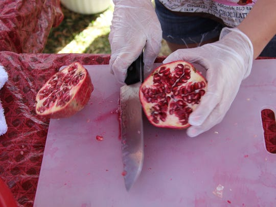 Abbie Evans, 11, Logandale shows off the ripe seeds of a pomegranate she cut open during the 2014 Pomegranate Arts Festival.