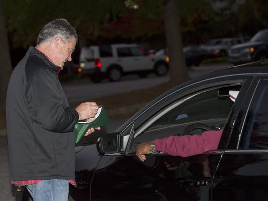 Steve Christian, a Booster Club parent at Greenville High School, jokes with a fan while taking up money for the available parking spots at Sirrine Stadium. Booster parents volunteer in the parking lot, the concession stands, the gate and in the press box.