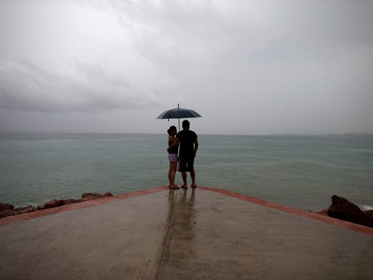 A couple looks out to sea as rainfall increases with