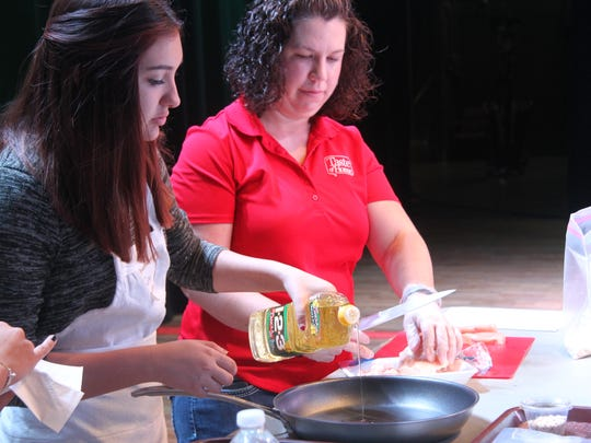Kristi Larson, a culinary specialist with Taste of Home, watches a student prepare a pan to sear chicken before Thursday night's Taste of Home Cooking School.