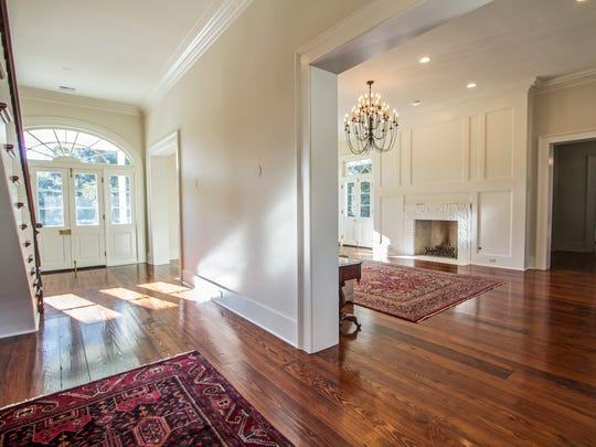 Antique wood floors and carved molding accent the foyer.