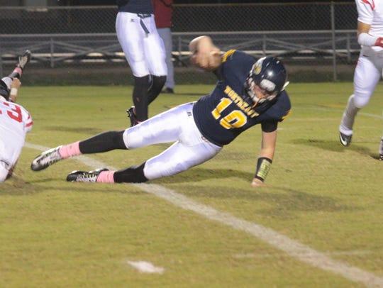 Northeast quarterback Benji Burchwell (10) falls forward