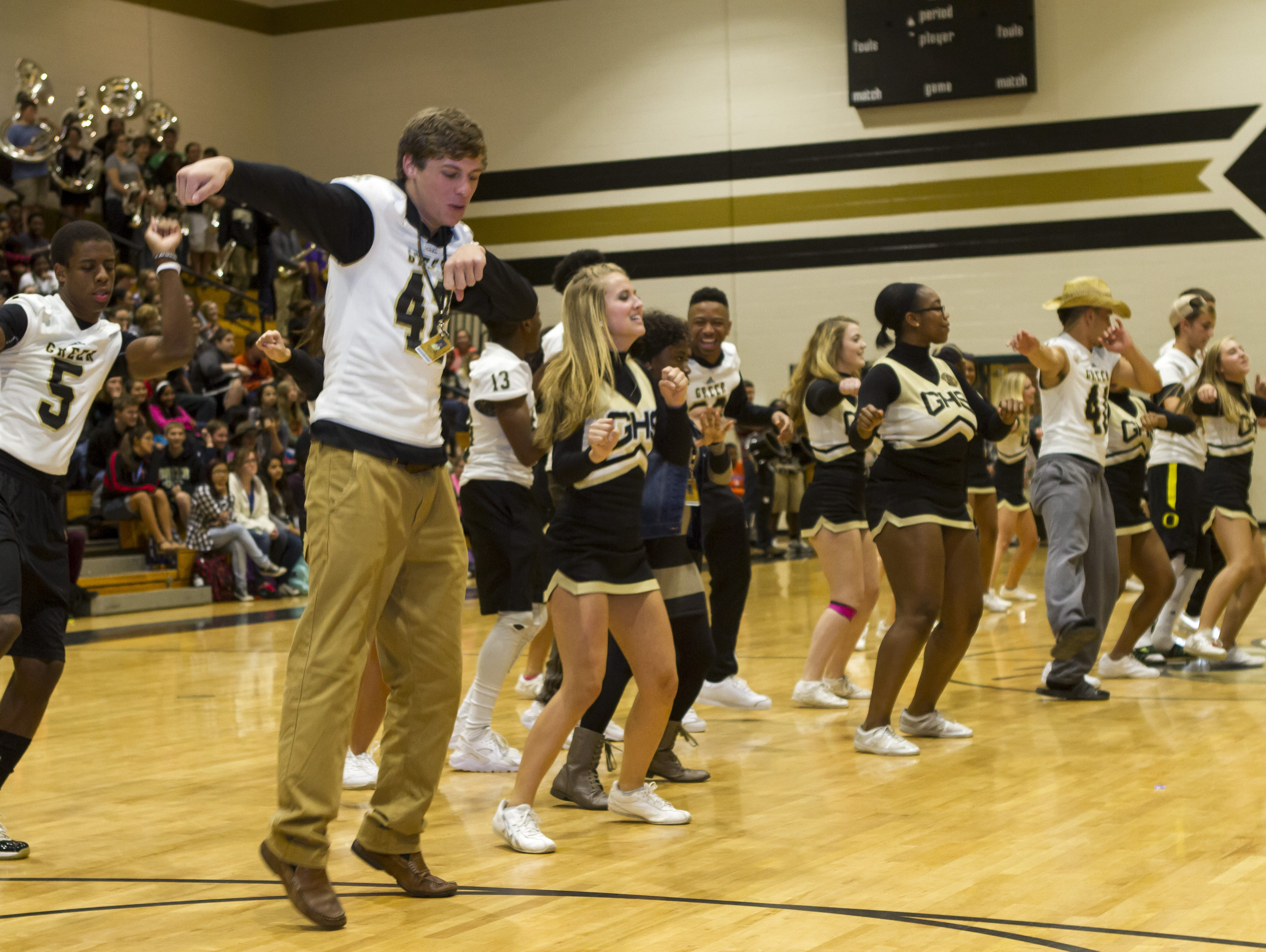 """Greer High School football players join the cheerleaders in a dance-off skit against """"rivals"""" dressed up as the Blue Ridge High School squad."""