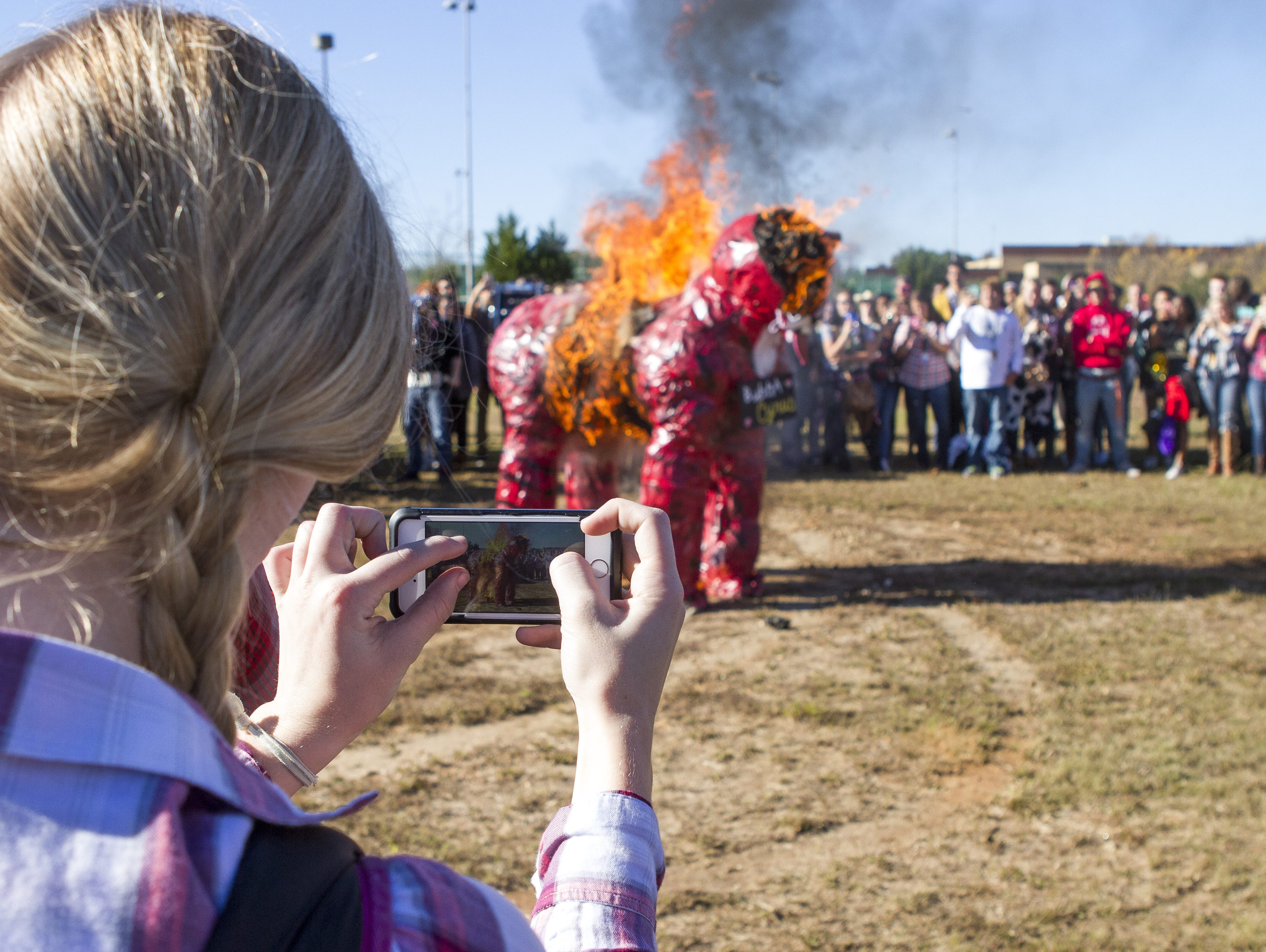 Greer High School freshman Caroline Littlefield zooms in on the action as Bubba Cyrus, the Blue Ridge High School mascot, burns. The Yellowjackets burn a tiger every year at the pep rally leading up to the rivalry game.