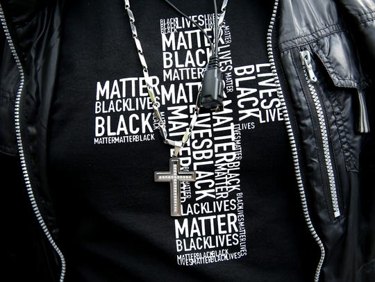 A detail view of a man's shirt that reads 'Black Lives