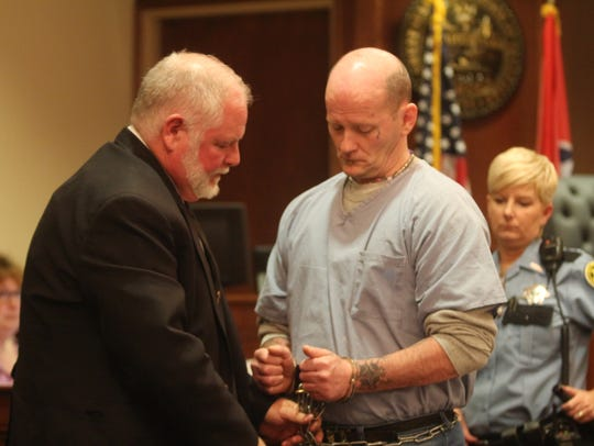 Lee Watts, center, is unchained before his sentencing