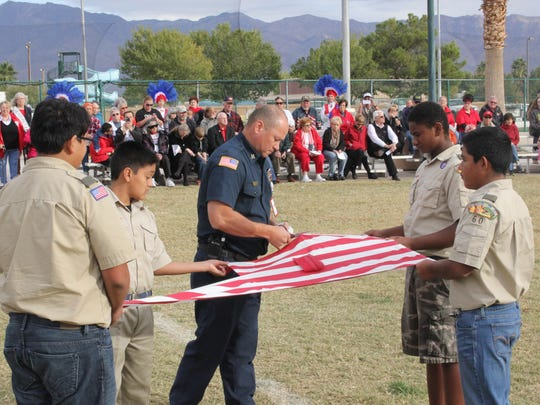Mesquite Fire and Rescue's William Martinez, assisted by Boy Scouts of Mesquite Troop 2060, cuts an American flag during the retirement ceremony Sunday.