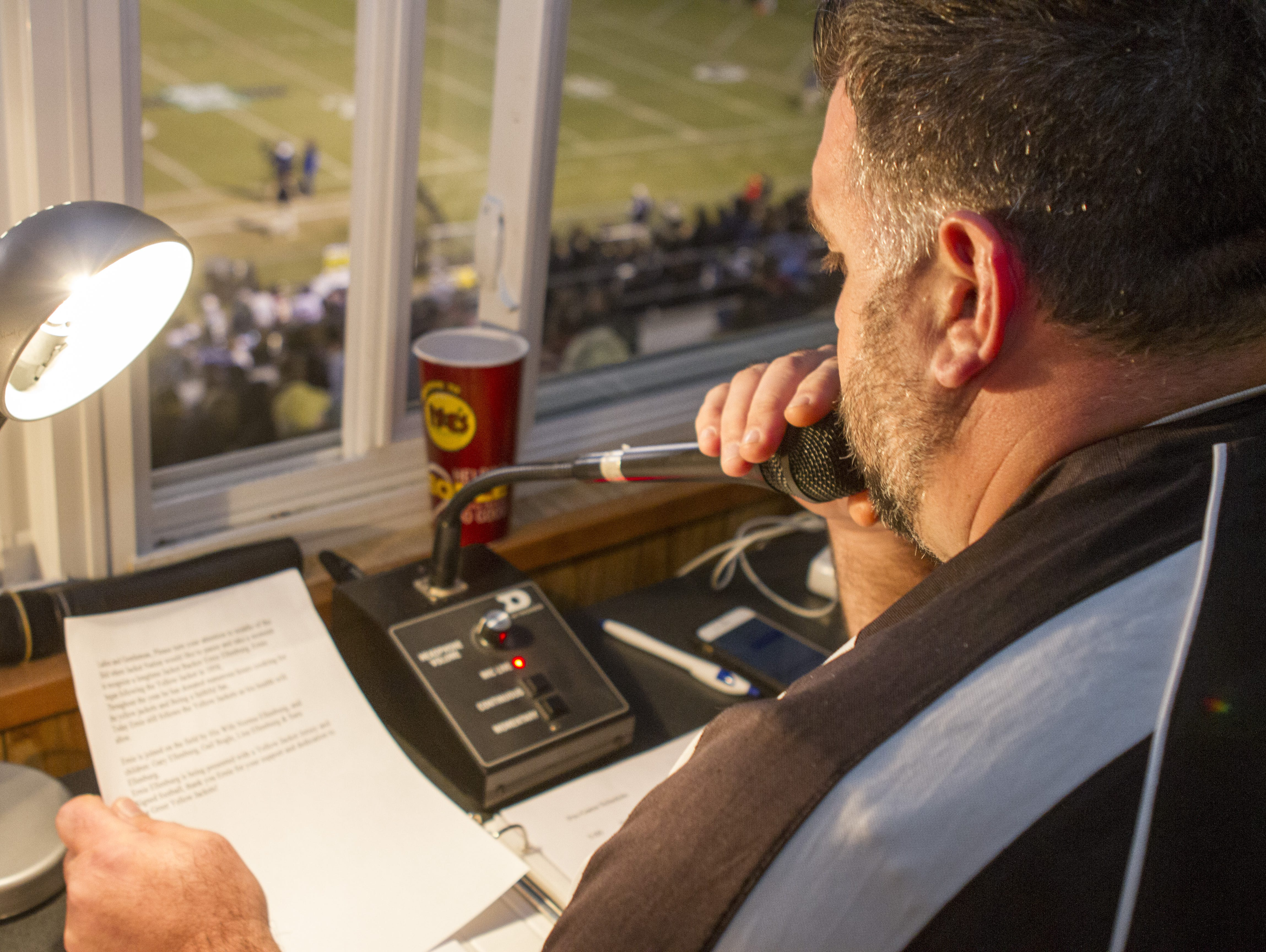 Chad Hannon, the public address announcer at Greer High School, reads off an advertisement before the game against Travelers Rest High School. The home Yellowjackets were able to win the game, scoring 45 straight points after going down 13-0.