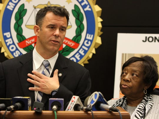 Acting Monmouth County Prosecutor Christopher J. Gramiccioni announced three men were charged with felony murder and other offenses related to the 2009 killing of Red Bank school teacher Jonelle Melton during a press conference. The victim's mother, Gwendolyn Cruse of Hamilton, stood next to him.